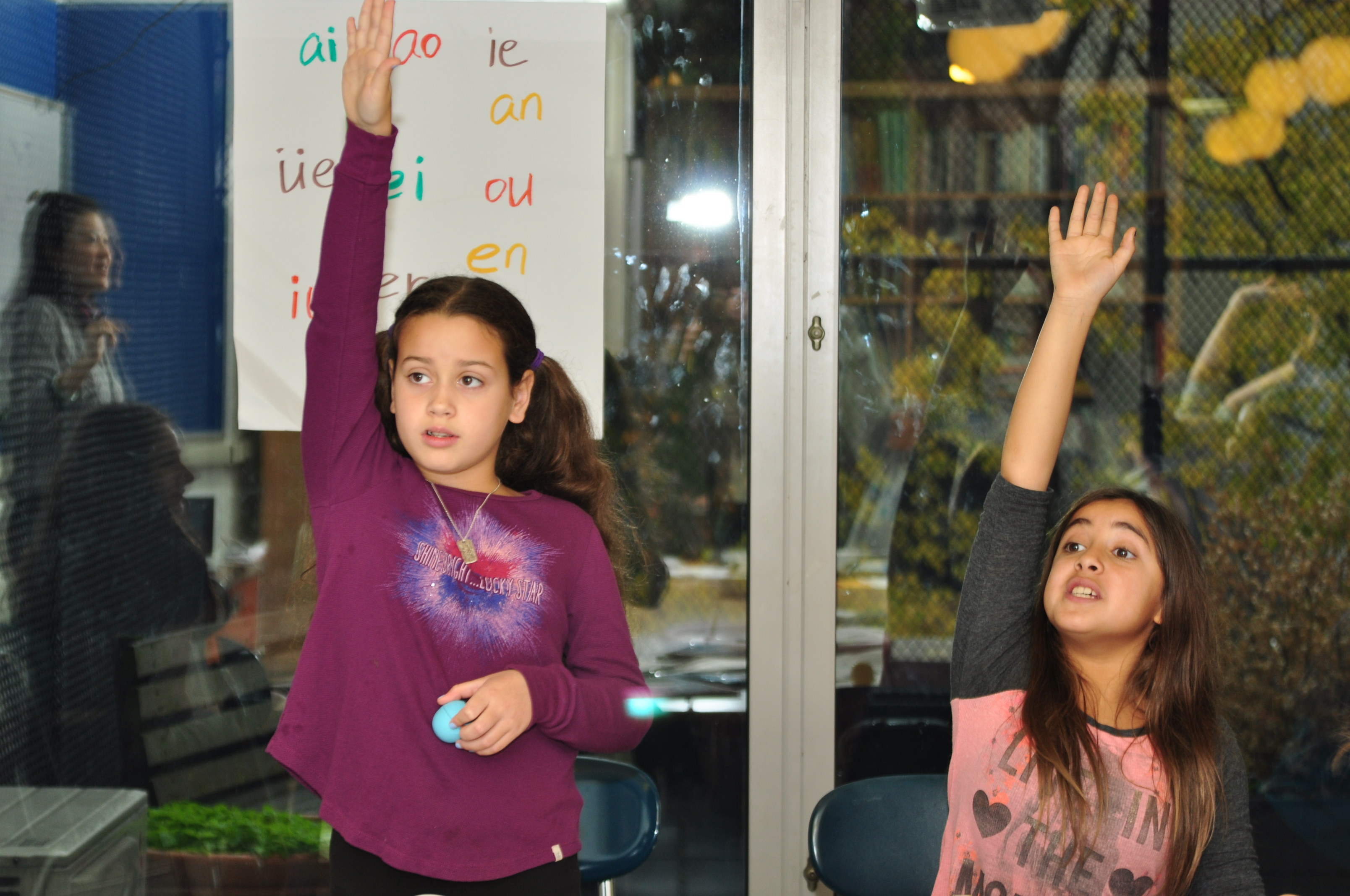 Middle School students raise their hands and show their enthusiasm to share their voice in the classroom.